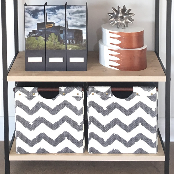 Use baskets or bins on the bottom of bookshelves to hold papers and paperback books. Click through for more styling tips.