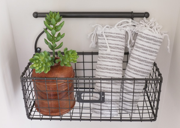 Use wall baskets in bathroom to hold toiletries and decor