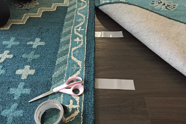 Use duct tape to hold two area rugs together