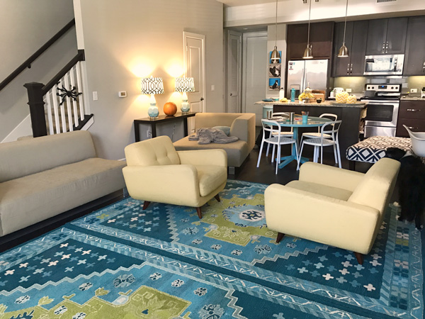 Furniture pushed out of the way in an apartment to put area rugs down