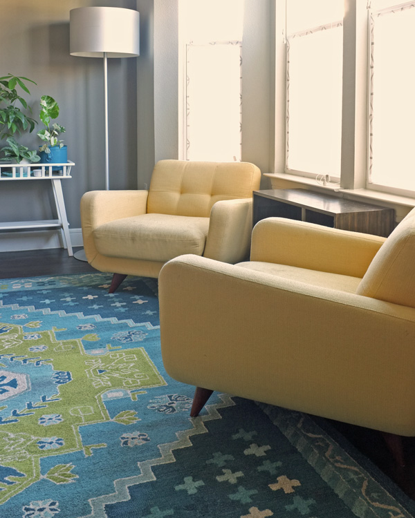 Rug under front legs of arm chairs