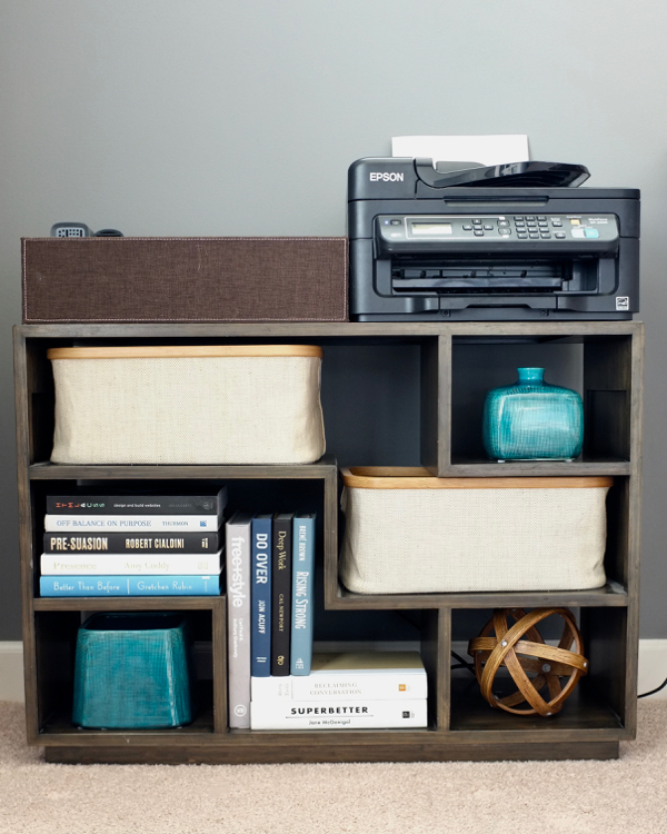 A small bookcase doubles as a printer stand and minimal office storage. The baskets hide charging cords and small computer equipment.