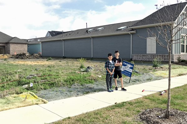 Our boys standing by the sold sign on our new house lot.